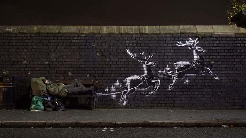 """Novo mural de Banksy mostra sem-abrigo a """"ser puxado"""" pelas renas do Pai Natal"""