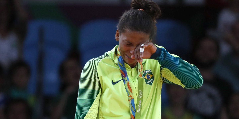 """Brasil: campeã olímpica de judo acusa polícia brasileira de racismo   A campeã olímpica brasileira de judo, Rafaela Silva, disse que foi parada pela polícia brasileira numa avenida movimentada do Rio de Janeiro na quinta-feira e tratada como um """"criminoso"""" por ser negra.   Silva, que ganhou ouro nos Jogos Olímpicos de 2016, disse que estava a caminho de casa, vinda do aeroporto do Rio de janeiro quando a polícia mandou parar o táxi em que seguia.  Numa série de publicações na rede social Twitter, Rafaela explica que mandaram-na sair do veículo e perguntaram-lhe onde trabalhava, enquanto o motorista foi interrogado separadamente.   Quando o agente a reconheceu, ela obteve permissão para ir embora.  O motorista disse à Rafaela que um dos agentes lhe perguntou se Rafaela tinha apanhado o táxi numa favela.   """"Isso tudo em plena Avenida Brasil, com todos a olharem para mim, pensando que a Polícia tinha apanhado algum bandido, mas era apenas eu, tentando chegar à casa"""", escreveu Silva.  """"Até onde vai este preconceito?"""", questionou."""