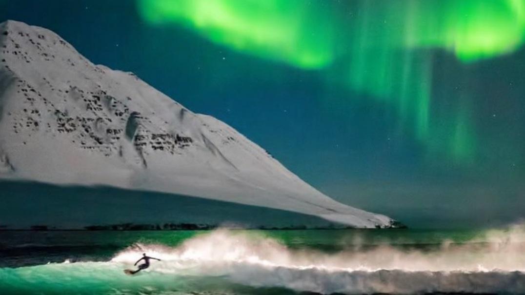 Surfar sob a luz da aurora boreal na Islândia